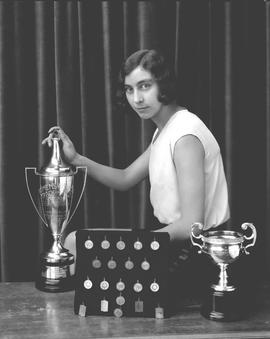 Norma Chiddy with track and field trophies and medals, Wetaskiwin, Alberta.