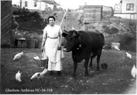 Woman with milk bucket, cow, and chickens, Crowsnest Pass area, Alberta.