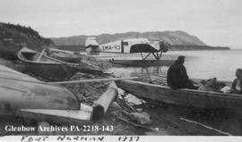 Airplane and boats on shore, Fort Norman, Northwest Territories.