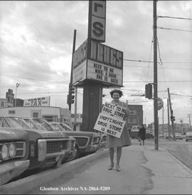 Mrs. Lillian Dick has objections to Super S Drugs signage and she protests, Calgary, Alberta.