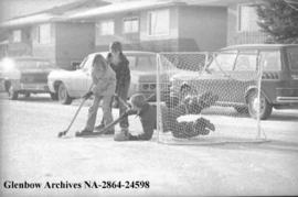 Children playing hockey on the street, Calgary, Alberta.