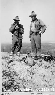 Malcolm Norris and Bert Wagonitz prospecting on rocky hilltop.