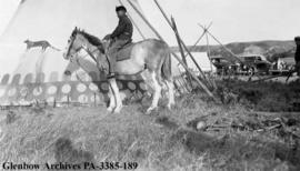 Tipi and boy on horse, Blackfoot (Siksika) reserve, Alberta.