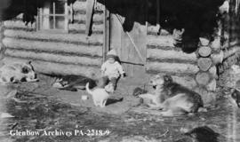 Billy Norris as a baby, sitting outside log cabin with cat and dogs.