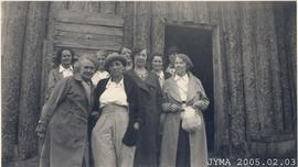 A group of women in front of a log structure.