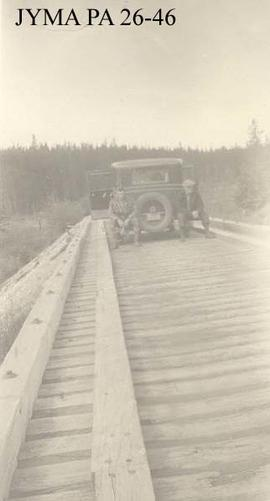 Car and two men on a wooden highway bridge, west of Jasper, Alberta.