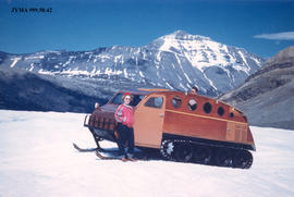 Helny Jeck in front of a Athabasca Glacier snowmobile, Columbia Icefields, Jasper National Park, ...