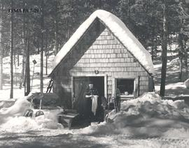 Fred Brewster in front of a cabin at Maligne Lake Chalet, Jasper National Park, Alberta.