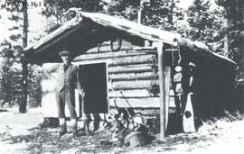 Daniel Alven Phillips in front of a log cabin.