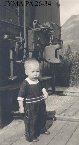 Child beside box car, Lucerne, British Columbia.