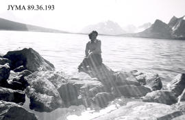 Woman sitting on rocks at water's edge, Jasper National Park, Alberta.