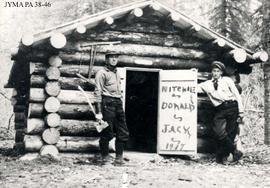 Curly Phillips and Jack Hargreaves posing in front of cabin near Entrance, Alberta.