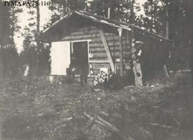 A man and dogs in front of a log cabin.