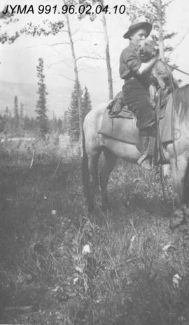 [Woman on horse with dog], Alberta