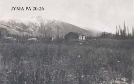 A homestead with log cabins, location unknown.