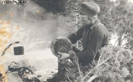 Unknown man cooking on an open campfire.