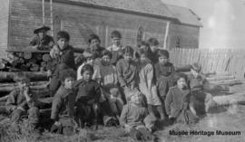 Children on logs in front of Le Goff, Cold Lake church, Alberta