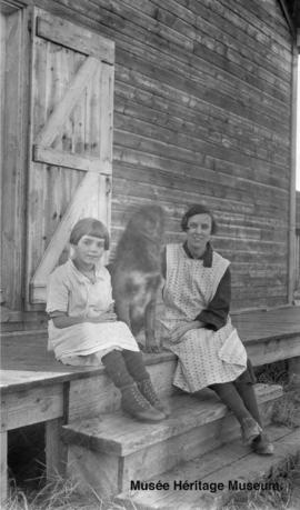 Girls and dog at side of Le Goff, Cold Lake school, Alberta