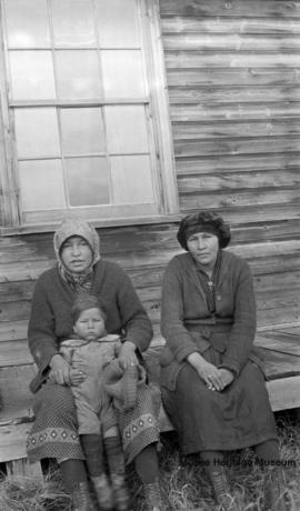 Two women and child in front of Le Goff, Cold Lake school, Alberta