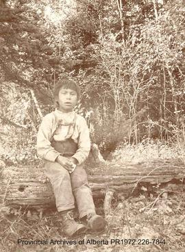 First Nations boy sitting on a log in a wooded area in the Lake of the Woods, Ontario area