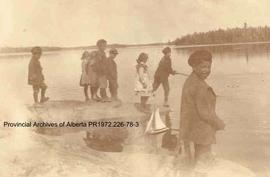 First Nations children playing with a toy sailboat at the waters edge in the Lake of the Woods, Ontario area