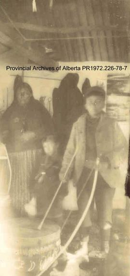 First Nations family, indoors, with drum, in the Lake of the Woods, Ontario area