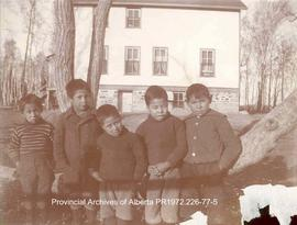 Five First Nations boys standing in front of the Presbyterian Mission house at Shoal Lake, Ontario