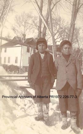 Two First Nations boys standing in front of the Presbyterian Mission house at Shoal Lake, Ontario