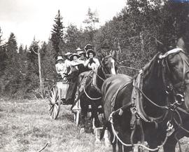 Group of 8 riding in a horse-drawn wagon in the countryside near Okotoks, AB.