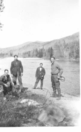 Four young men standing on the riverbank, either Sheep or Highwood River, AB.