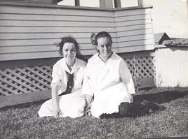 Two girls on the lawn of a house, possibly Daggett's, Okotoks, AB.