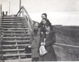 Four girls on steps leading to Upper High School, Okotoks, AB.