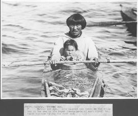 Canada. Hudson Bay. Father and son. This Esquimo has taken his child out to sea in his kayak (can...