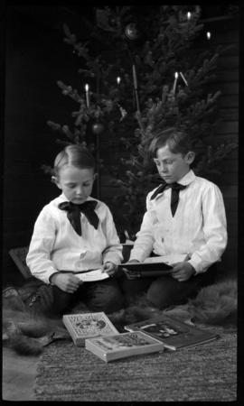 Elliott Jr. and Robert Barnes looking at photographs under Christmas tree