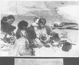 Canada. Hudson Bay. Esquimos eating in the interior of their igloo. Notice the soap stone kettle ...