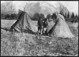 [Stoney Indian children with playhouse teepee at Kootenay Plains]